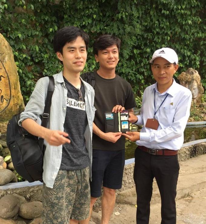 Đại diện BQL (phải) trao lại tài sản thất lạc cho du khách Lee Seung Hyeor (trái).