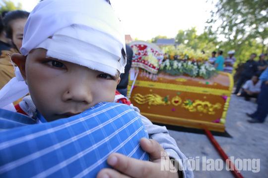 Cháu Vỹ (6 tuổi) quấn khăn tang và băng vết thương ở trán.