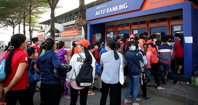 Công nhân xếp hàng chờ rút tiền từ máy ATM chiều 28.1