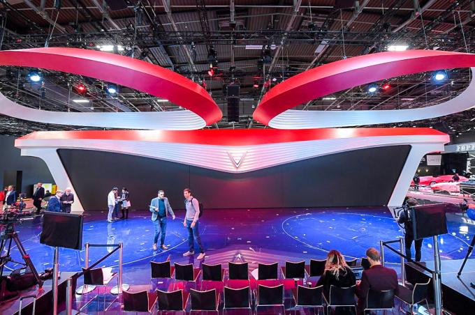 """Logo hình chữ V nằm chính giữa sân khấu, hai cánh trải ra hai bên mô phỏng đèn xe """"mắt hi"""" của VinFast. Viền đỏ chạy dài tại phần sải cánh của màn hình đem lại cảm giá mới mẻ, tràn đầy năng lượng."""