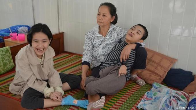 Người mẹ đang phải chăm sóc hai đứa con bị di chứng chất độc da cam. Ảnh: dw.com