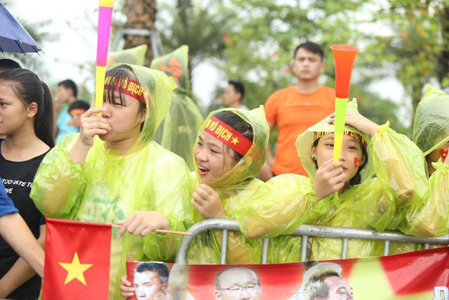 Cổ động viên đội mưa chờ đón những người hùng đội Olympic.