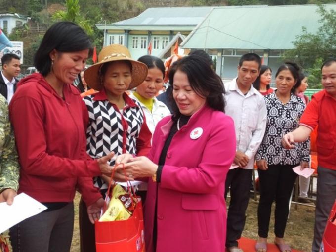 Bà Nguyễn Thị Xuân Thu - Chủ tịch Trung ương Hội Chữ thập đỏ Việt Nam trao quà cho bà con bản Chiềng.