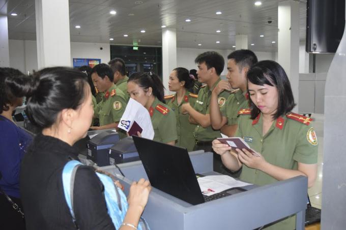 Cán bộ Phòng Quản lý xuất nhập Cảnh Công an tỉnh Thừa Thiên Huế phối hợphướng dẫn cho hành khách thực hiện thủ tục xuất nhập cảnh.