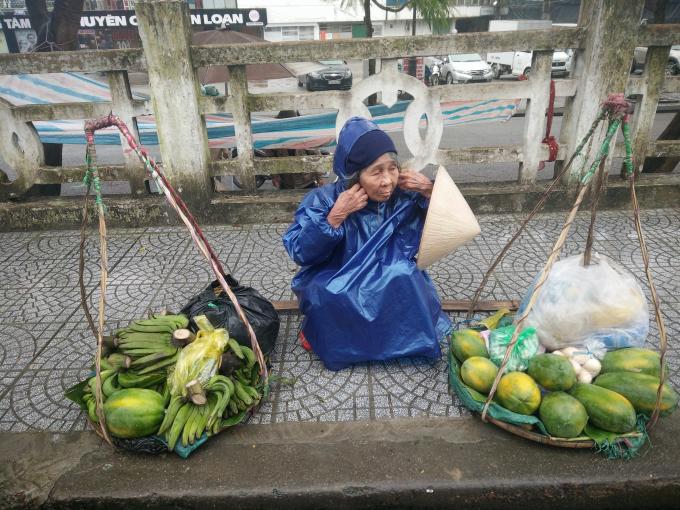Cầu Tràng Tiền, cụ bà bán hàng chống chọi với giá lạnh. (Ảnh: Như Quỳnh)