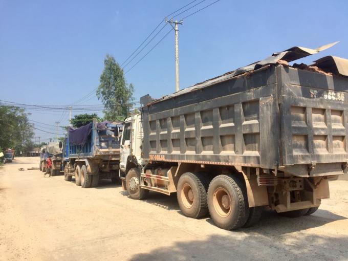 Nhiều xe chở đất được che bạt sơ sài khiến đất đá rơi vãi xuống đường gây bụi bặm.