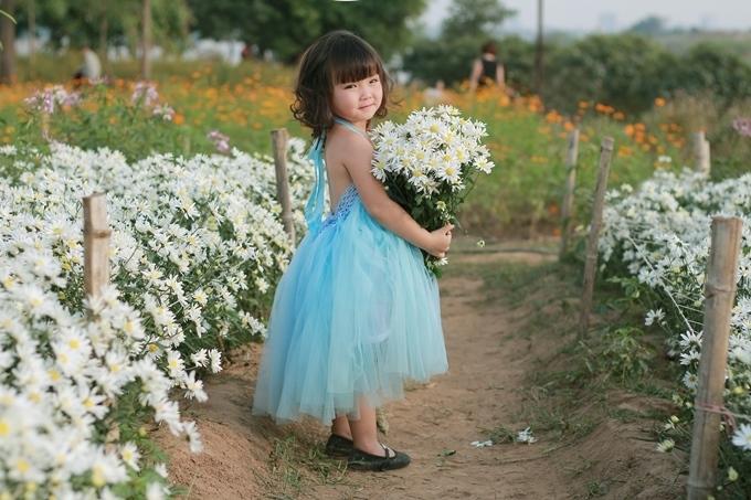 Dù nhỏ tuổi nhưng Phương Nhi đã biết tạo dáng trước ống kính, biết hòa mình vào những sắc hoa để dưới góc chụp của nhà nhiếp ảnh, bé như một thiên thần làm ngây ngất lòng người.