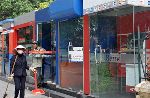 Nhân viên dọn dẹp vệ sinh tại chuỗi ATM trên đường phố Hà Nội. Ảnh: A.Q.