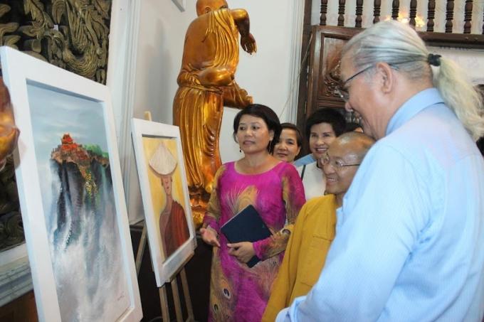Họa sĩ Đàm Thủy giới thiệu các bức tranh cho hòa thượng Thích Nhật Từ, ông Nguyễn Trọng Cơ cùng du khách.
