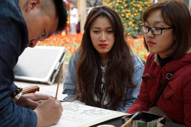 Hai bạn trẻ chăm chú theo dõi ông đồ viết thư pháp bằng chữ quốc ngữ.