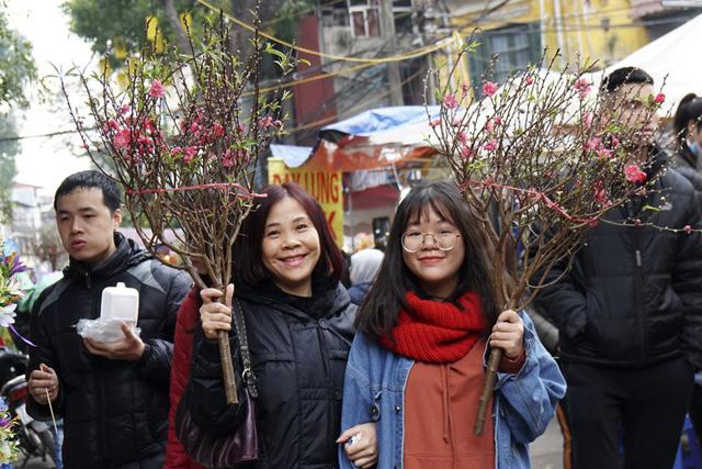 Vẻ phấn khởi của những vị khách mua được cành đào vừa ý trong chợ hoa Hàng Lược.