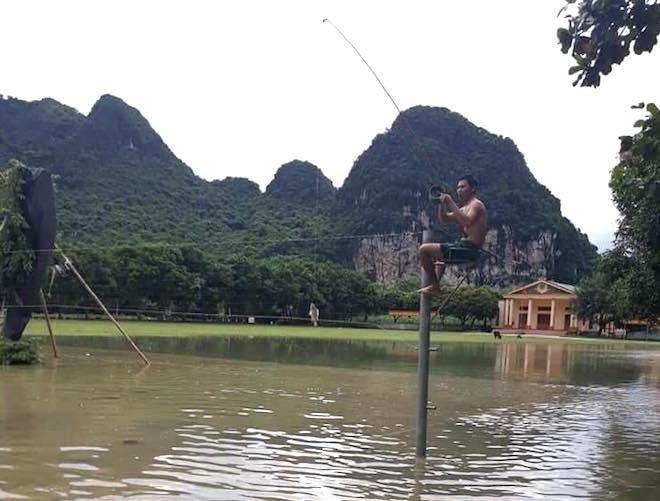 Một người dân ngồi câu cá ngay trên sân bóng chuyền.