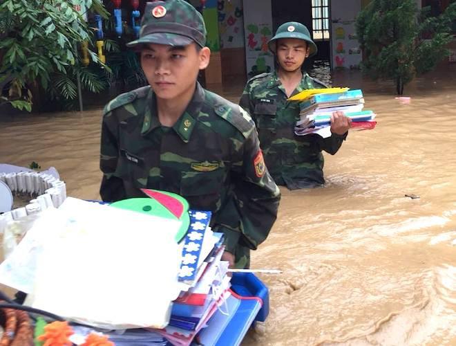 Giúp trường mầm non di chuyển tài sản, thiết bị dạy học ra khỏi ngập lụt.(Ảnh: Hải Thượng).
