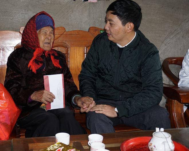 Phó tổng biên tập Trần Đức Vinh thăm hỏi, tặng sổ tiết kiệm cho bà mẹ Việt Nam anh hùng Hoàng Thị Sinh.