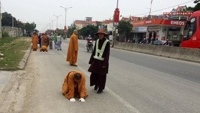 """Hai vị Đại đức thực hiện """"tam bộ nhất bái"""" trên Quốc lộ 1A -qua địa phận thị trấn Cầu Giát, huyện Quỳnh Lưu, Nghệ An - Ảnh: H.Tình"""