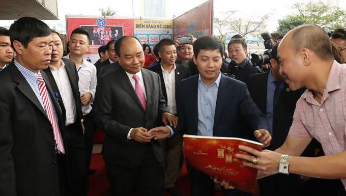 Phó Tổng biên tập Báo Pháp luật Việt Nam Trần Đức Vinh giới thiệu các ấn phẩm báo Pháp luật Việt Nam với Thủ tướng Nguyễn Xuân Phúc.