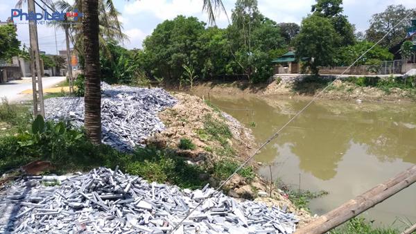 Sau chấm dứt tình trạng xả thải gây ô nhiễm kênh dẫn nước, hộ sản xuất Hùng Nhung tiếp tục đổ đá thải lấn bờ kênh. (Ảnh: Anh Thắng)