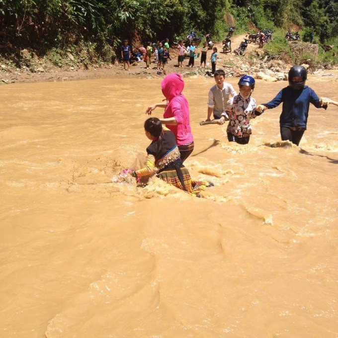 thày cô giáo và các em học sinh phải dìu dắt nhau qua những con suối dữ.