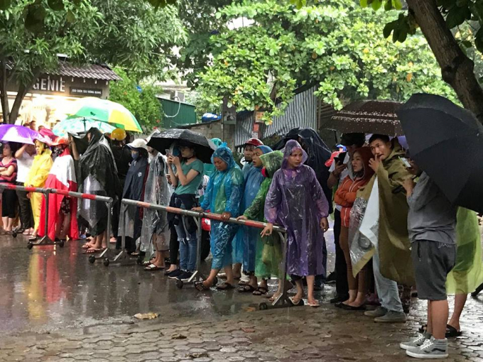 Người dân đội áo mưa theo dõi vụ vây bắt đối tượng.