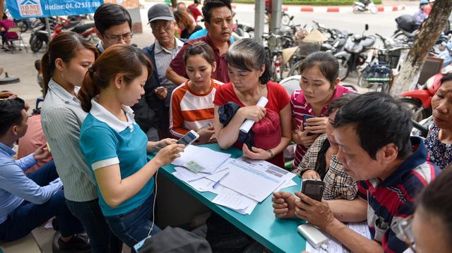 Do người dân đến làm thủ tục quá đông, điểm giao dịch phải kê bàn ra ngoài vỉa hè để kịp phục vụ khách hàng.
