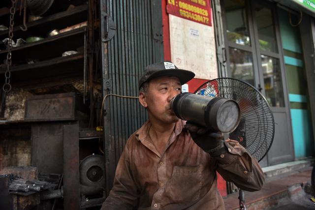 Thỉnh thoảng ông lại nghỉ tay uống ngụm nước giải khát rồi lại tiếp tục làm việc.
