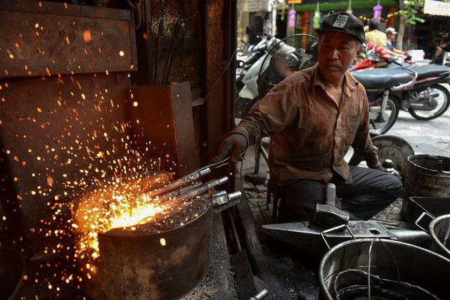 Nắng nóng trên 40 độ C, thêm hơi nóng từ chiếc lò nung hơn 1.000 độ C tỏa ra nhưng ông Hùng vẫn miệt mài làm việc.