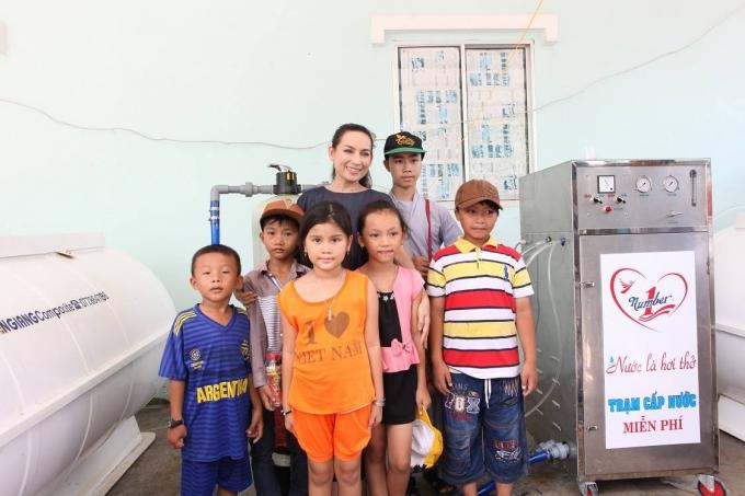 Ca sĩ Phi Nhung chụp ảnh lưu niệm cùng trẻ em địa phương trong hành trình trao máy lọc nước mặn thành nước ngọt cho người dân đồng bằng sông Cửu Long.