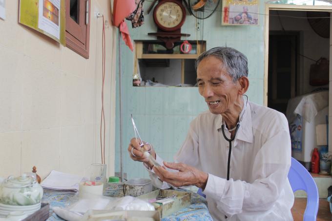 Lương y Đào Việt Kế đang dưới thiệu về những dụng cụ thường dùng trong chữa bệnh của ông.