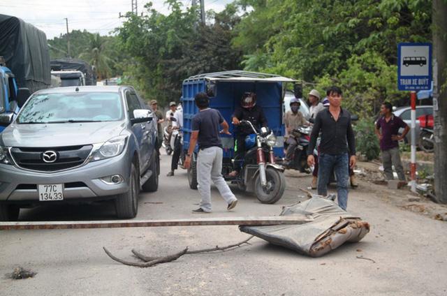 Bức xúc vì từng đoàn xe tải chạy gây bụi, dân đem cây chặn đường cấm xe tải lưu thông.
