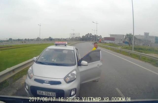 Tài xế taxi mở cửa xuống xe tiến về phương tiện chặn đầu phía trước
