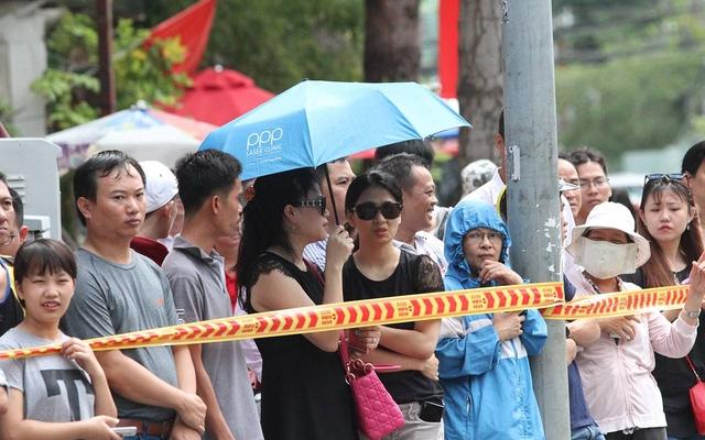 Người dân đứng dọc hai bên đường chờ đón Tổng thống Mỹ. (Ảnh: Dân trí)