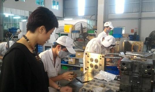 Chủ tịch Công ty Phan Thị Minh kiểm tra dây chuyền sản xuất linh kiện cơ khí xuất khẩu.