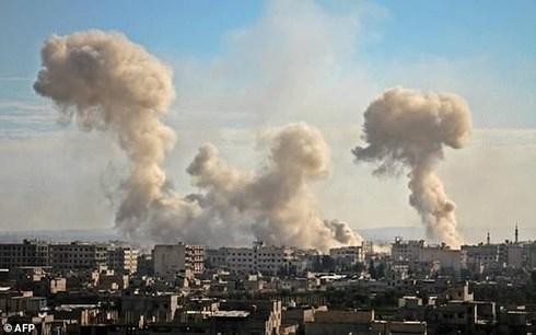 Khói bốc lên từ những tòa nhà ở làng Mesraba, Đông Ghouta sau một đợt dội bom ác liệt. Ảnh: AFP