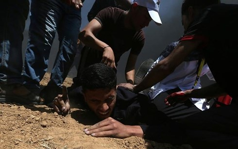 Người Palestine bị thương do trúng đạn pháo từ lực lượng an ninh Israel. Ảnh: Reuters