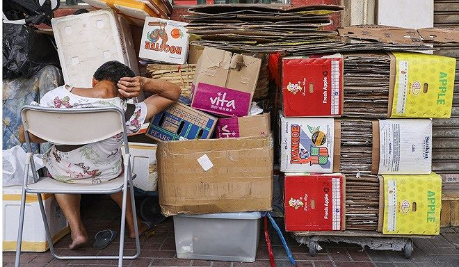 Một người cao tuổi ngủ gục bên các tấm bìa các tông ở To Kwa Wan