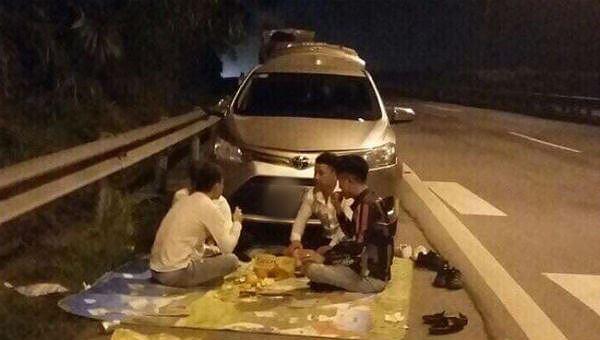 Nhóm thanh niên trải bạt ăn uống trên đường cao tốc
