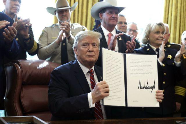 Tổng thống Trump ký văn bản phủ quyết đầu tiên. (Ảnh: Reuters)