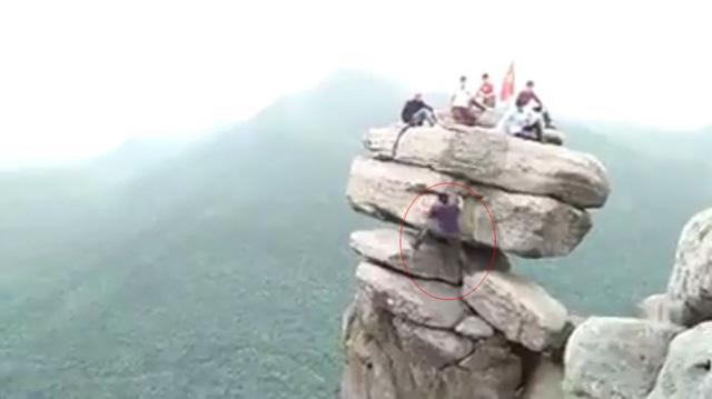 Nhóm bạn trẻ trèo lên mỏm đá cheo leo mà không sử dụng dụng cụ bảo hộ. Ảnh chụp màn hình