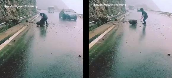 Ngườithanh niênđội mưa đẩy viên đá vào lề đường.