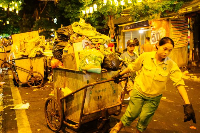 Phải nghiêng mình gần 60 độ người công nhân vệ sinh này mới có thể làm chiếc xe rác chuyển động.