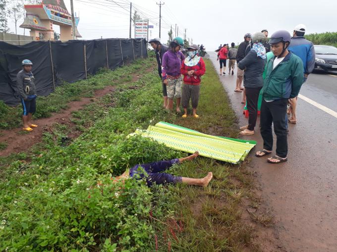 Người đàn bà nằm chết bên vệ đường và rất đông người dân hiếu kỳ đứng xen