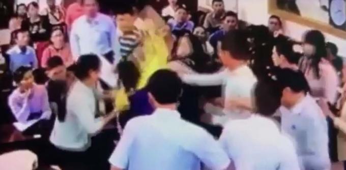 Trần Thị Phi Yến (áo khoác vàng) đang hành hung bà Mỹ Anh bằng túi xách cầm trên tay tại phiên đấu giá. (ảnh cắt từ clip).