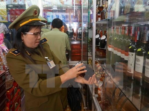Lực lượng quản lý thị trường kiểm tra một cửa hàng kinh doanh rượu. Ảnh: Phạm Cường/TTXVN