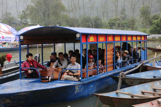 Du khách ngồi trên thuyền tham quan cảnh đẹp của khai hội Chùa Hương.