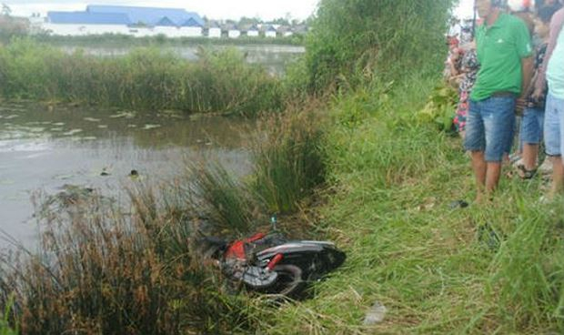 Chiếc xe máy hư hỏng nằm dưới bờ vuông tôm.