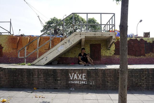 Một phụ nữ phải trú tạm dưới bóng mát của gầm cầu thang khi trên đường không một bóng cây.