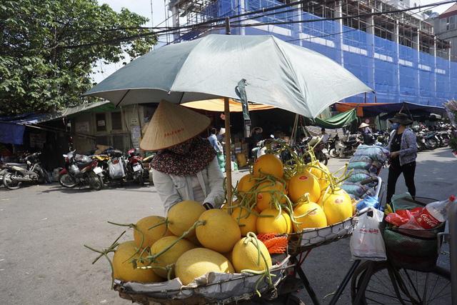 Người bán hoa quả trang bị khăn áo đầy đủ và cắm chiếc ô trên xe để tránh hỏng hoa quả trong thời tiết khắc nghiệt.