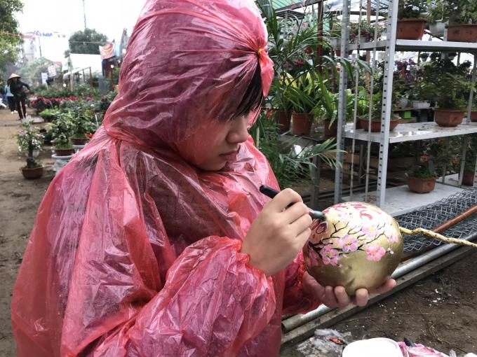 Một cô gái dầm mưa để trang trí cho quả dừa, tạo thành món hàng độc bán tết.