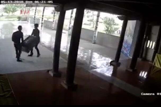 Hình ảnh hai tên trộm rinh chiếc hòm công đức ra ngoài được camera ghi lại (ảnh cắt từ clip).