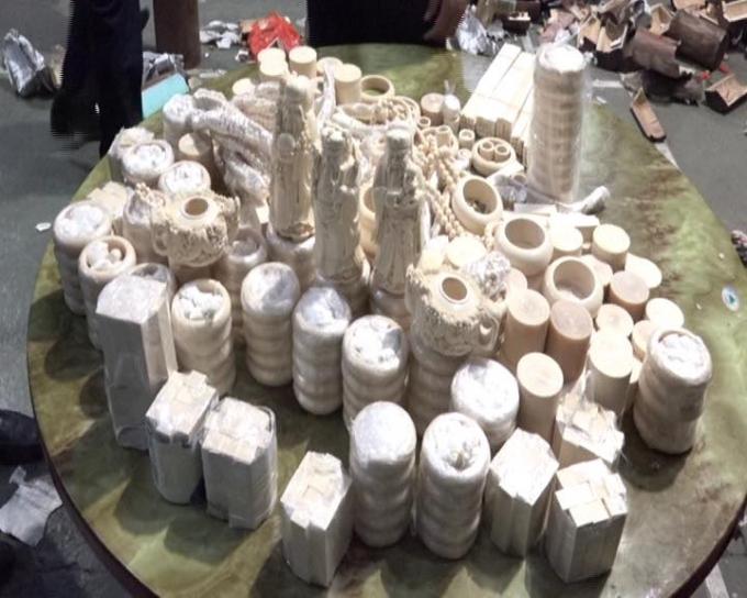 Số lượng đồ mỹ nghệ nghi là ngà vọi được trà trộn trong 33 khúc gỗ rỗng được lực lượng chức năng bắt giữ. Ảnh cơ quan chức năng cung cấp.